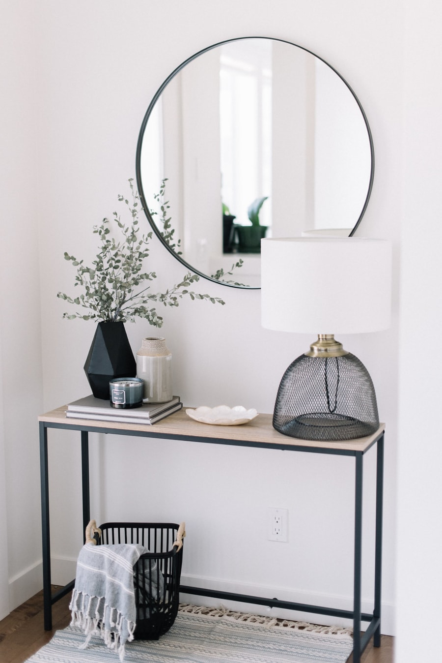 A modern front entryway using black accents on a slim table. Black framed circular mirror hangs above the table.